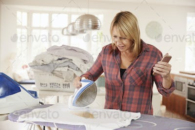 Distracted middle aged woman burns t shirt while ironing