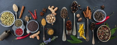 Variety of colorful spices and herbs on black stone background, top view, banner