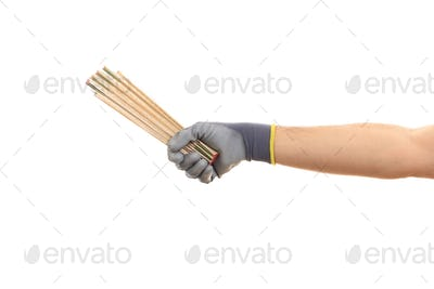 Gloved hand holding a wooden meter on white background