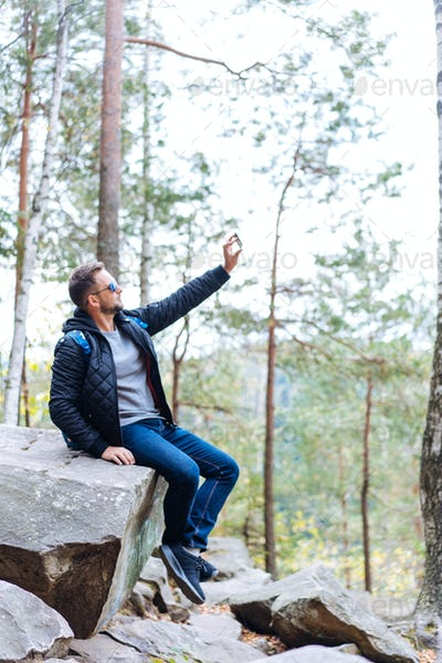 guy sits in the woods on a rock
