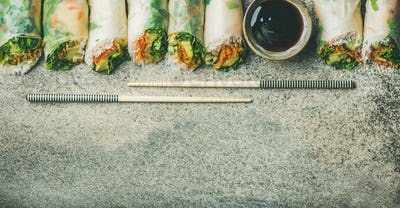 Vegan spring rice paper rolls over concrete background, copy space