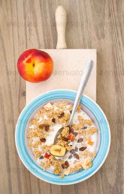 aerial shot of bowl of cereal with fresh peach on natural wooden