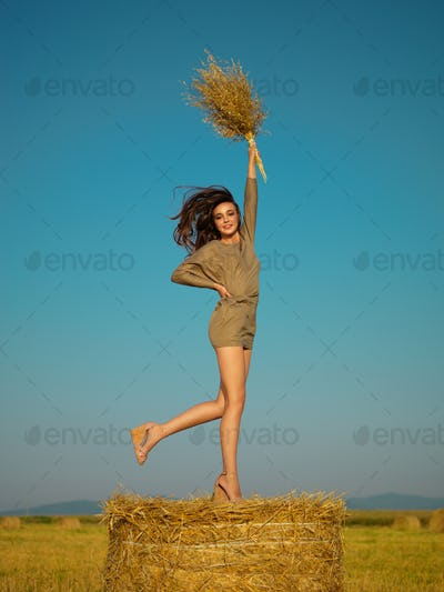 joyful young woman jumping on hay stack
