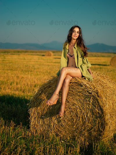 beautiful woman sitting on hay stack