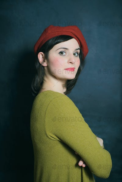 woman in green dress and red beret on the black wall background