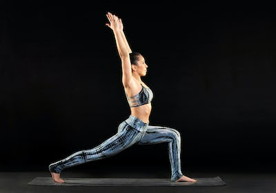 Woman practicing yoga doing a crescent lunge