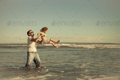 Father and son playing on the beach at the day time. Concept of