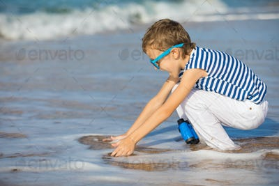 One happy little boy playing on the beach at the day time