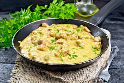 Meat stewed with cream in pan on burlap