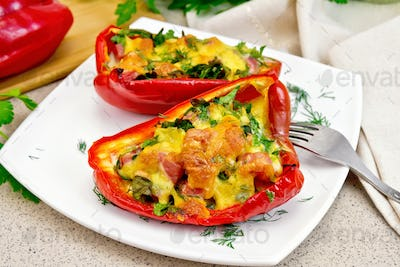 Pepper stuffed with sausage and cheese in white plate on table