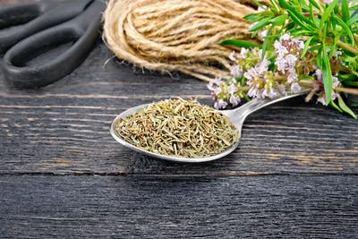 Thyme dry in spoon with scissors on board