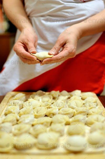 Woman making russian dumplings (pelmeni)