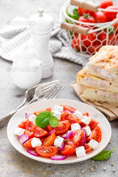 Tomato salad with fresh red onion and feta cheese. Healthy eating