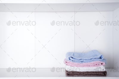 Stack of colorful bath towels on light background