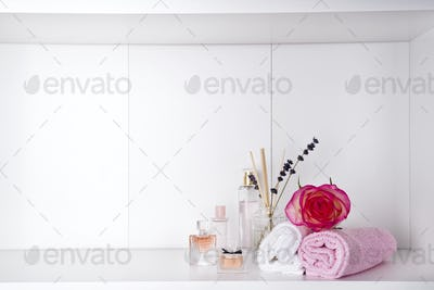 Stack of bath towels with rose and parfums on light background