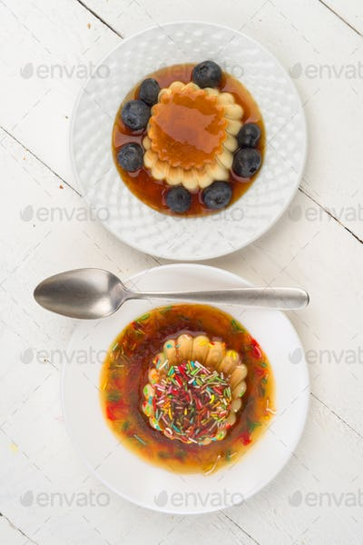 overhead shoot of two puddings on plate, in modern white wooden table