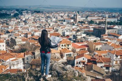 Young girl standing in front of beautiful city view and looking