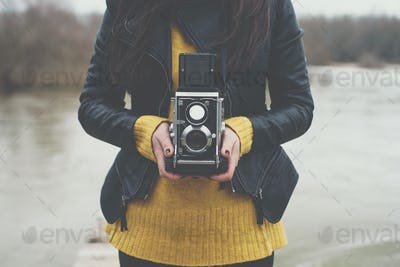 Young woman taking photographs with vintage retro camera