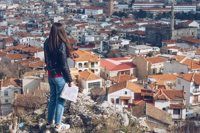 Young girl standing in front of beautiful city view. Panoramic v