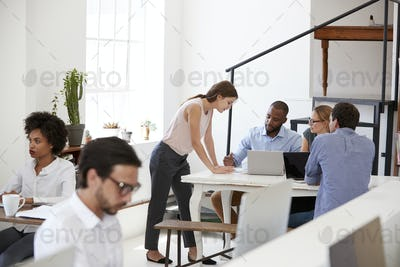 Woman working with colleagues at a desk in open plan office