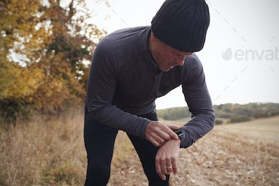 Mature Man On Autumn Run Around Field Checks Activity Tracker