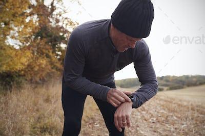 Mature Man On Autumn Run Around Field Checks Activity Tracker