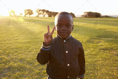 African elementary school boy making peace sign