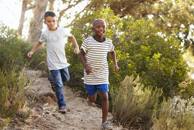 Two happy young boys running down a forest path