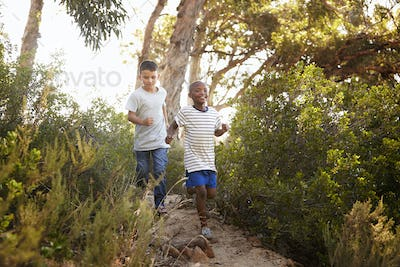 Two smiling young boys running down a forest path