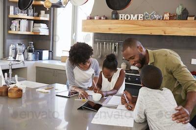 Parents Helping Children With Homework In Kitchen