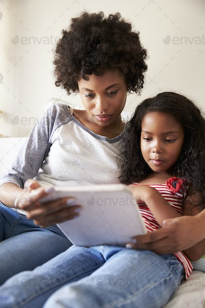 Mother And Daughter Siting On Bed Using Digital Tablet
