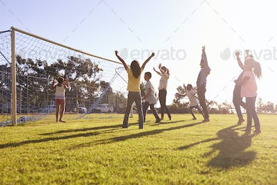 Families cheering scoring a goal during a football game