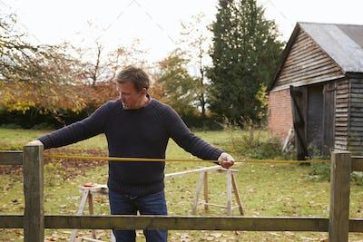 Mature Man Measuring Garden Fence For Repair