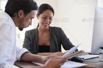 Man and woman looking at documents in an office, close up