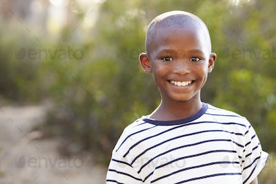 Smiling young black boy looking to camera outdoors
