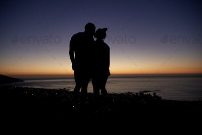 Couple standing and kissing by the sea at sunset on the beach