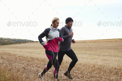 Mature Couple Running Around Autumn Field Together
