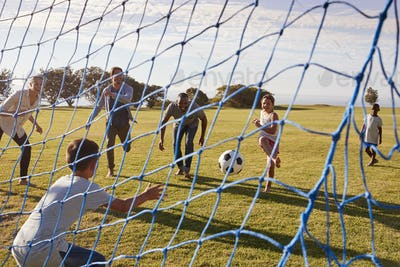 Two families playing football in park seen through goal net