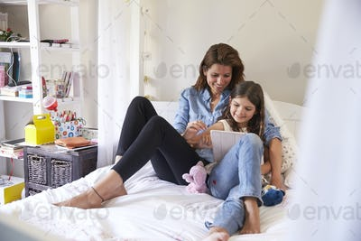 Mother And Daughter Sitting On Bed Using Digital Tablet