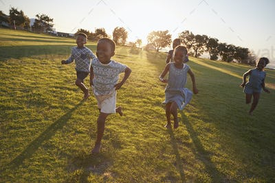 Elementary school kids running to camera in an open field