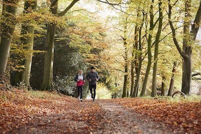 Mature Couple Running Through Autumn Woodland Together