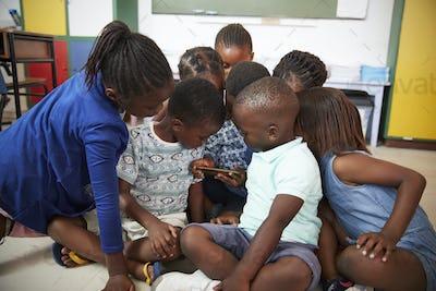 Elementary school kids sitting on floor looking at a book