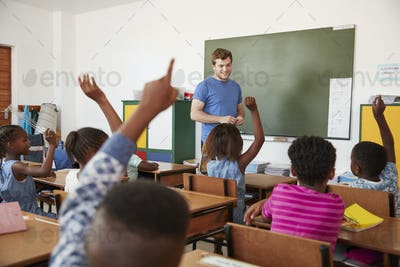 Kids raising hands to teacher in an elementary school class