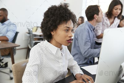 Young woman working at computer in a busy open plan office