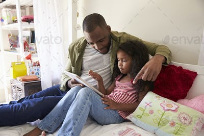 Father And Daughter Siting On Bed Using Digital Tablet