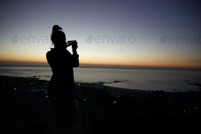 Woman taking photo with phone on beach, silhouette at sunset