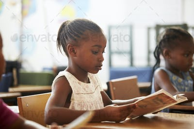 Girl holding book and reading in an elementary school lesson