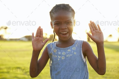 Portrait of African elementary school girl with hands raised