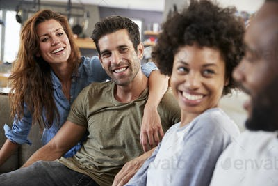 Couple Sitting On Sofa With Friends At Home Talking