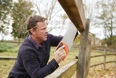 Mature Man Fixing Outdoor Fence With Saw
